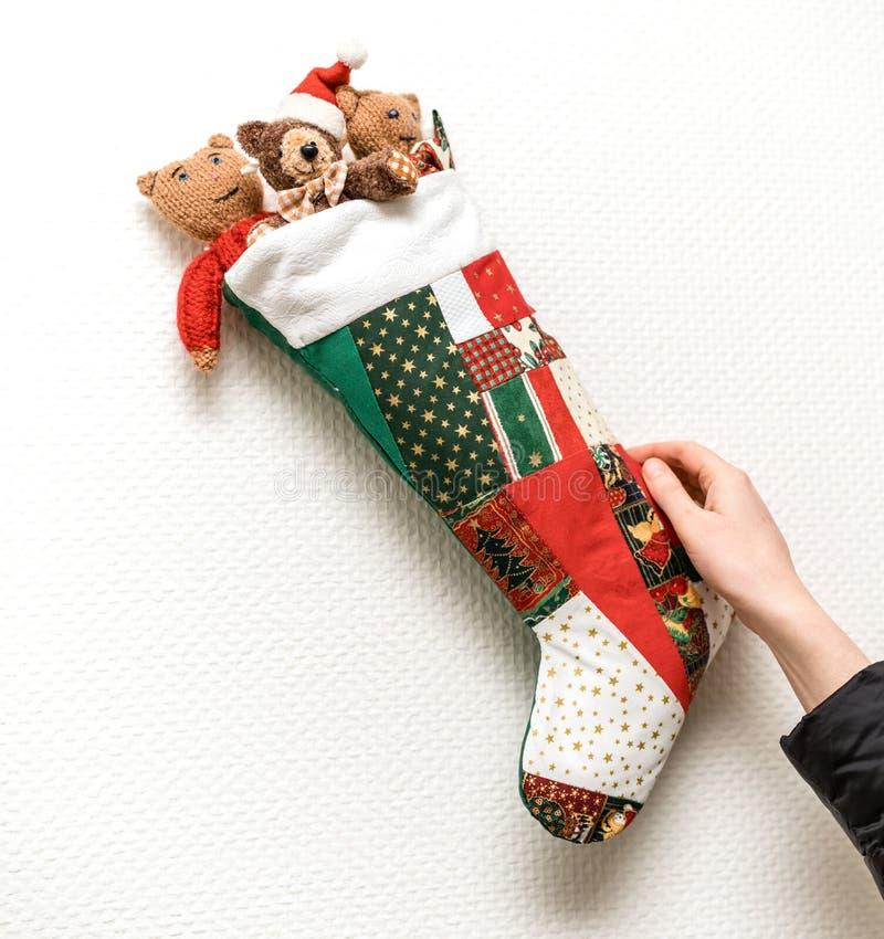 Frau, die auf der Wand den Weihnachtsstrumpf vereinbart stockbilder