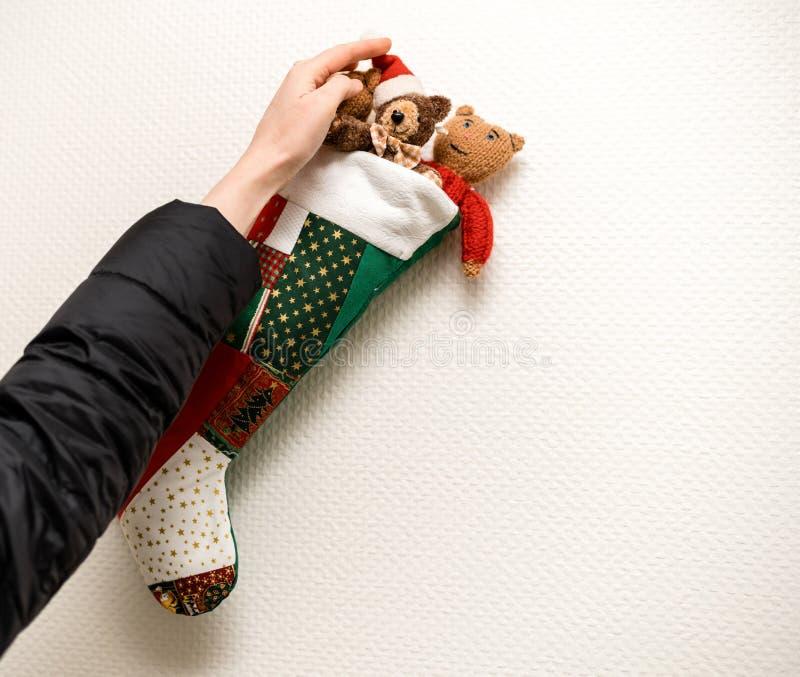 Frau, die auf der Wand den Weihnachtsstrumpf vereinbart stockfoto