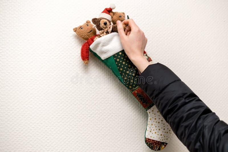 Frau, die auf der Wand den Weihnachtsstrumpf vereinbart lizenzfreie stockfotos