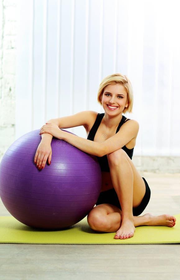 Frau, die auf der Yogamatte mit fitball sitzt stockfotos