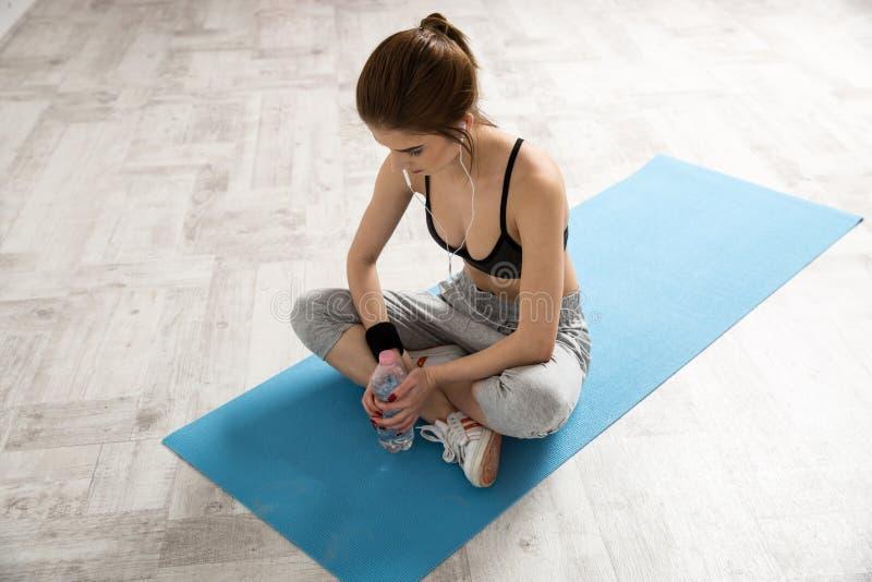 Frau, die auf der Yogamatte mit Flasche Wasser sitzt lizenzfreies stockfoto