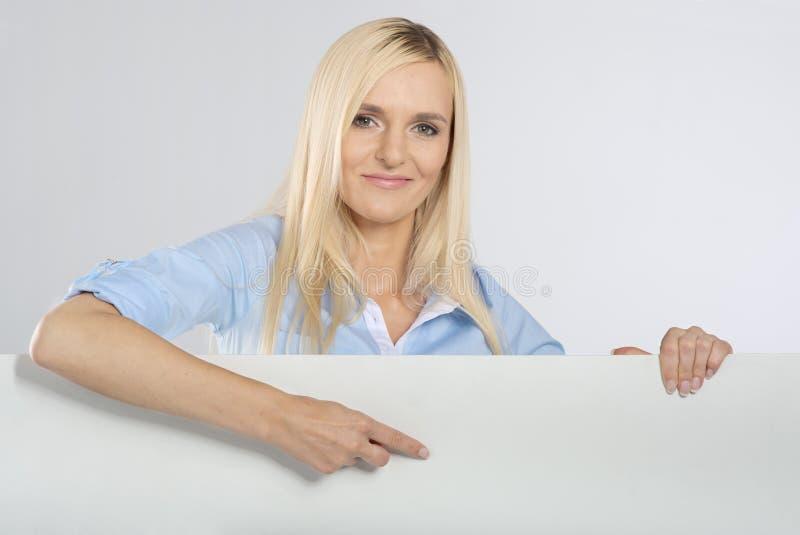 Frau, die auf ein Schild zeigt stockbild