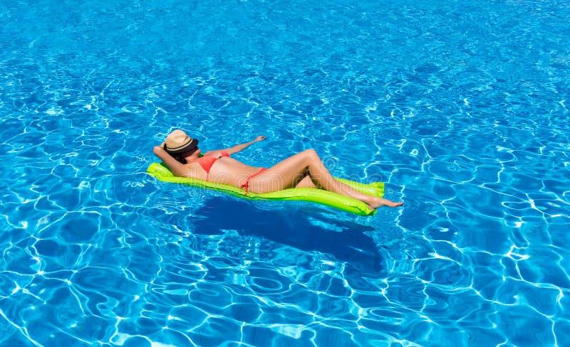 Frau, die auf eine Matratze in einem Swimmingpool schwimmt stockbilder