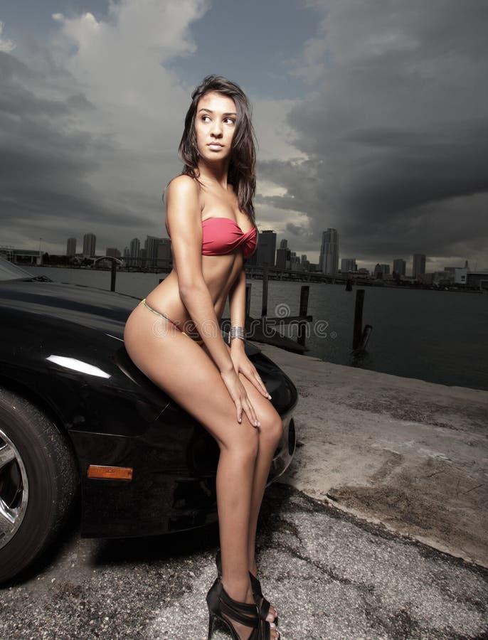 Frau, die auf einem Auto aufwirft stockfotografie