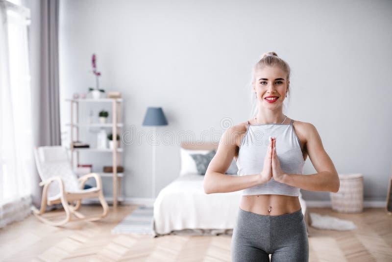 Frau, die auf einem Bein balanciert, Baumyogahaltung tut und zu Hause meditiert lizenzfreie stockbilder