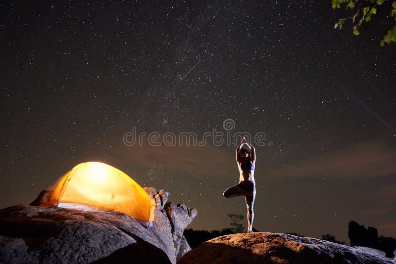 Frau, die auf einem Bein mit den angehobenen Armen tun Yoga nachts auf enormem Flussstein steht stockfotos