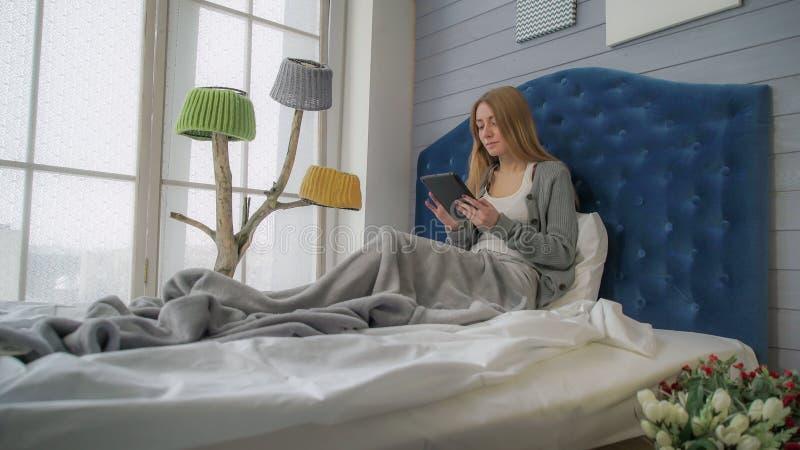 Frau, die auf einem Bett mit einer Tablette sitzt lizenzfreie stockfotos