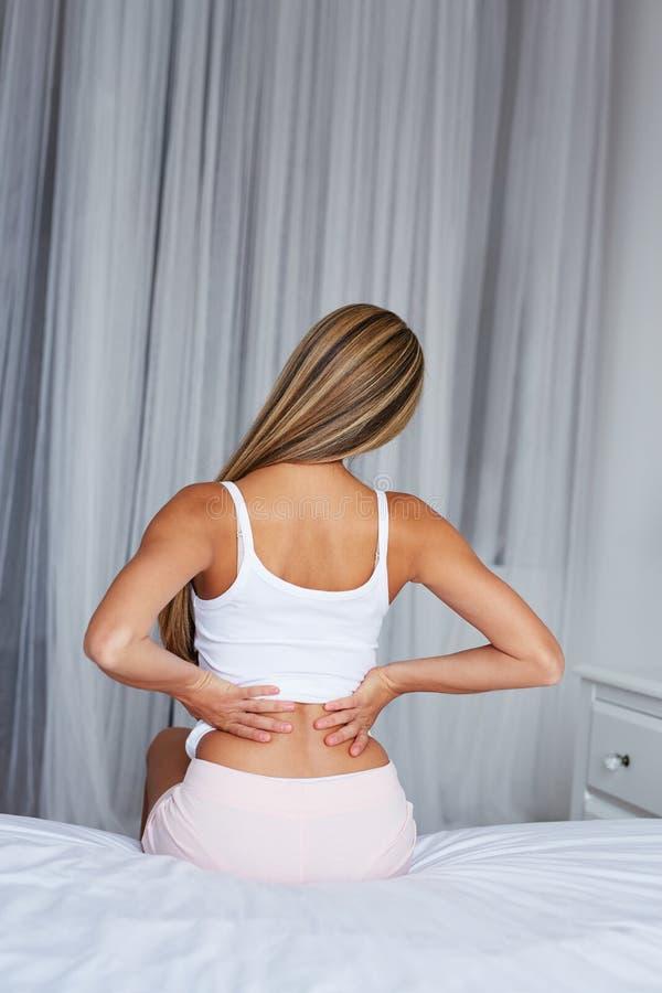 Frau, die auf einem Bett mit Rückenschmerzen sitzt lizenzfreies stockbild