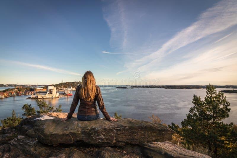 Frau, die auf einem Felsen betrachtet den Fjord und die Stadt in Kristiansand sitzt stockfoto
