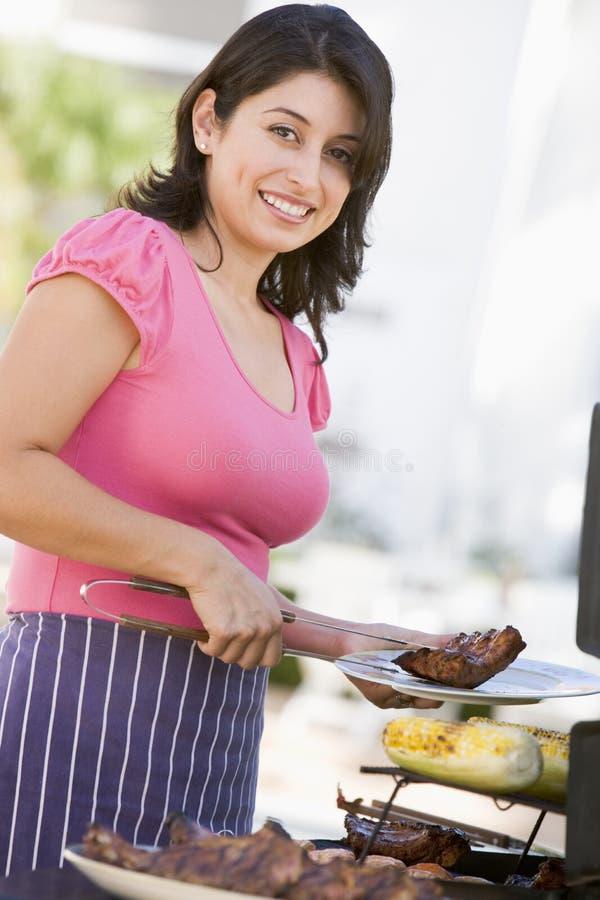 Frau, die auf einem Grill kocht lizenzfreies stockfoto