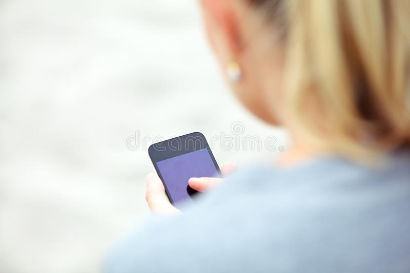 Frau, die auf einem Handy texting ist stockfoto