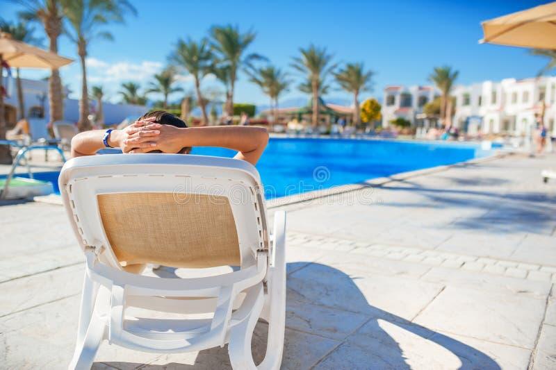 Frau, die auf einem Ruhesessel durch das Pool im Hotel liegt stockbild