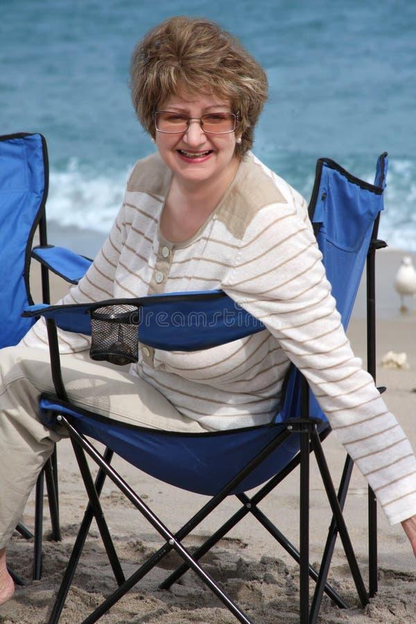 Frau, die auf einem sandigen Strand sich entspannt stockbilder