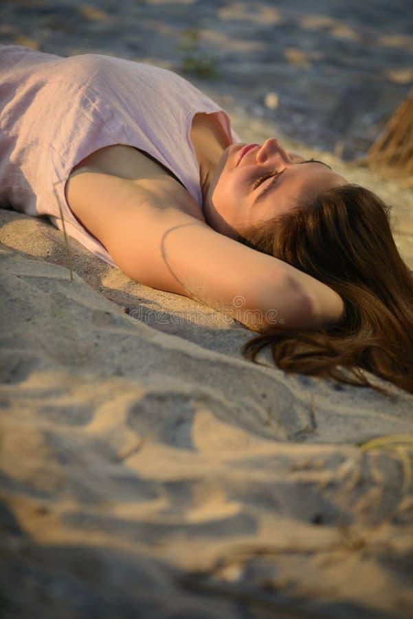 Frau, die auf einem Sandstrand auf Sonnenuntergang niederlegt stockfoto