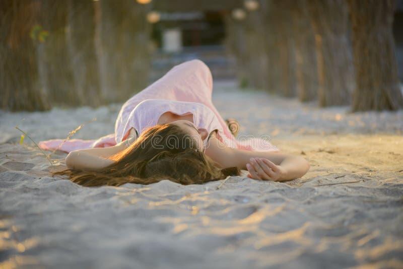 Frau, die auf einem Sandstrand auf Sonnenuntergang niederlegt lizenzfreie stockfotos