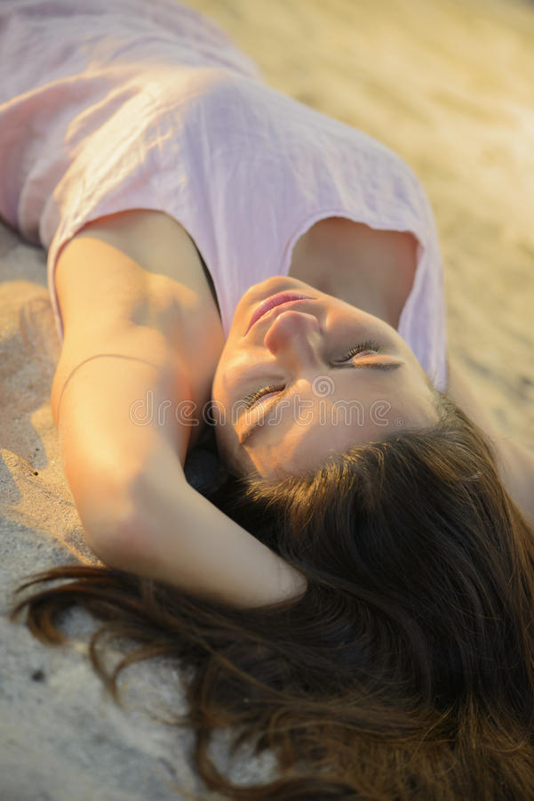 Frau, die auf einem Sandstrand auf Sonnenuntergang niederlegt stockbild