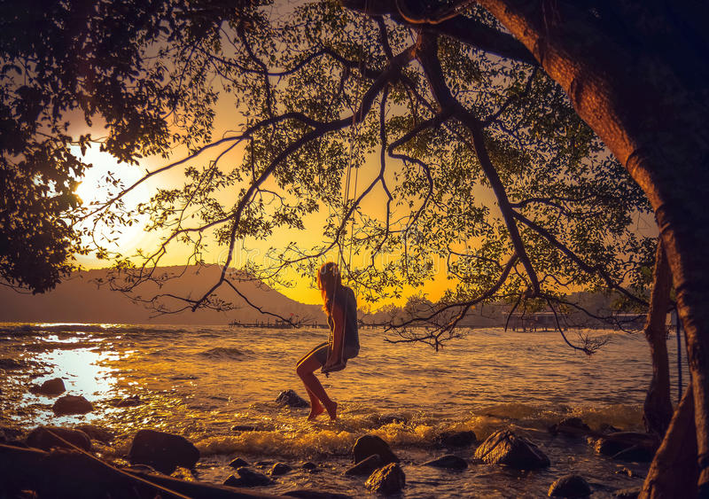 Frau, die auf einem Schwingen auf dem Strand sich entspannt lizenzfreie stockfotos