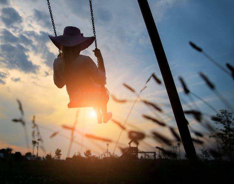Frau, die auf einem Schwingen bei Sonnenuntergang spielt stockfotos