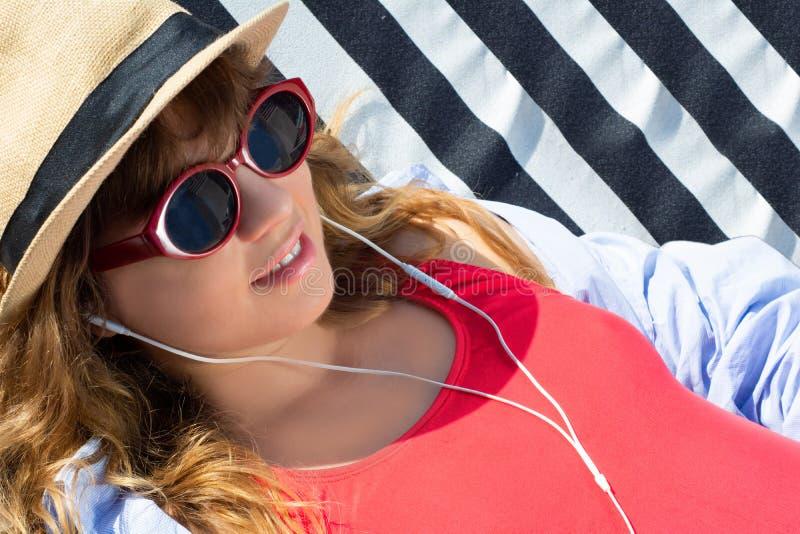 Frau, die auf einem Sonnenruhesessel sich entspannt lizenzfreie stockbilder