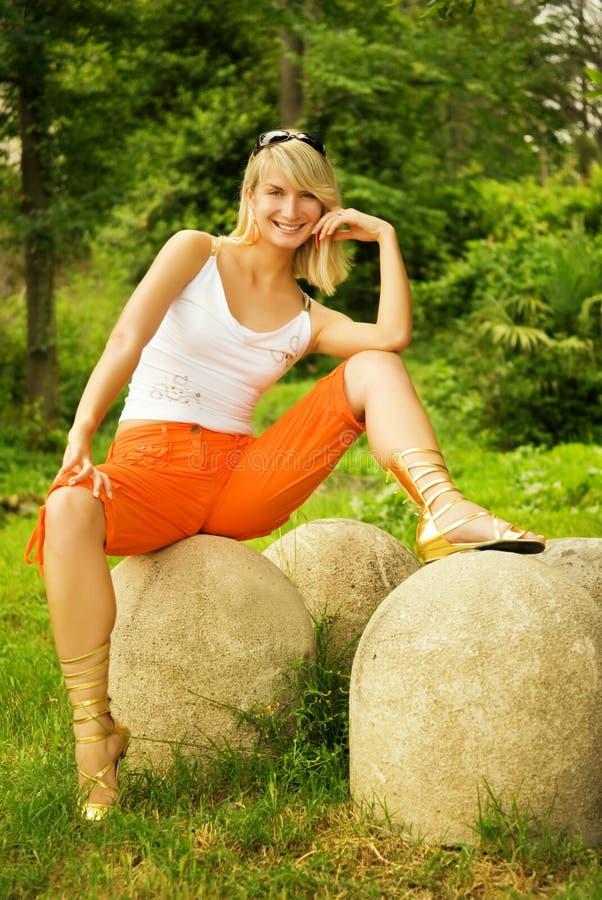 Frau, die auf einem Stein sitzt stockfotos