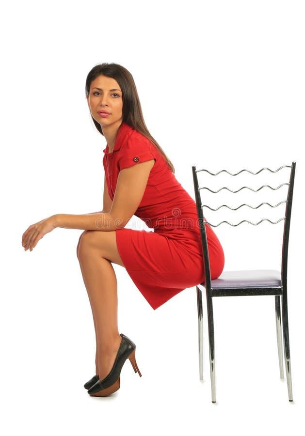Frau, die auf einem Stuhl, Profil sitzt stockbild