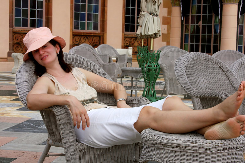 Frau, die auf einem Stuhl sich entspannt stockfotografie