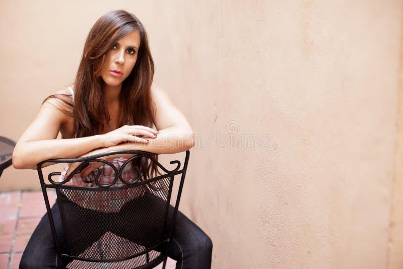 Frau, die auf einem Stuhl sitzt lizenzfreie stockfotografie