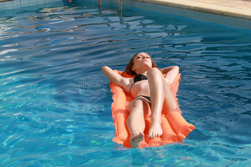 Frau, die auf einer aufblasbaren Matratze im Pool sich entspannt stockbilder