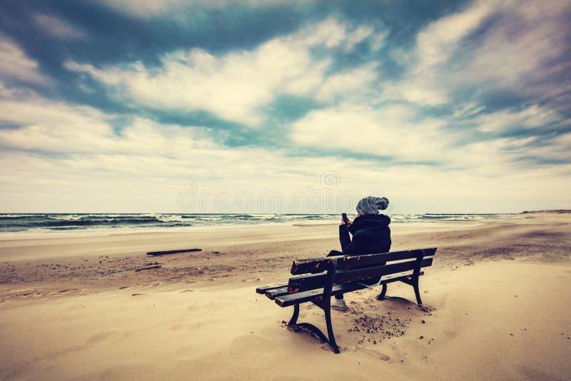 Frau, die auf einer Bank auf dem Strand unter Verwendung ihres Telefons sitzt stockfotografie