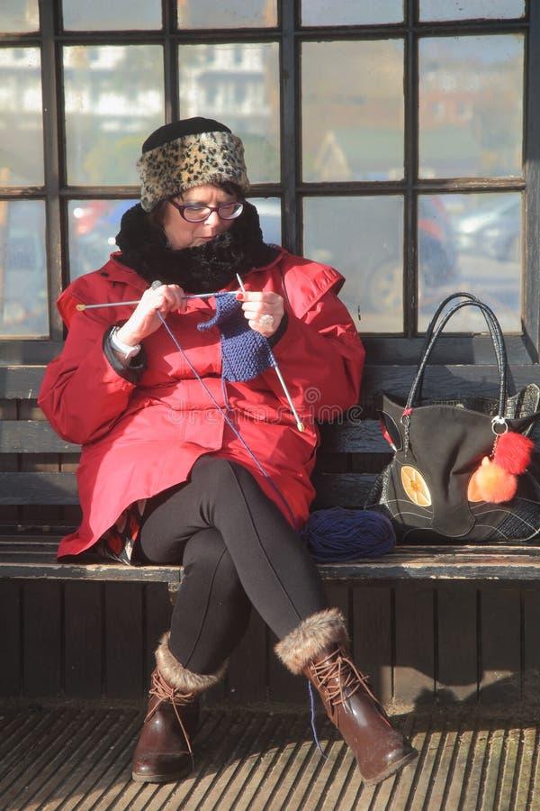 Frau, die auf einer Bank strickt stockfotos
