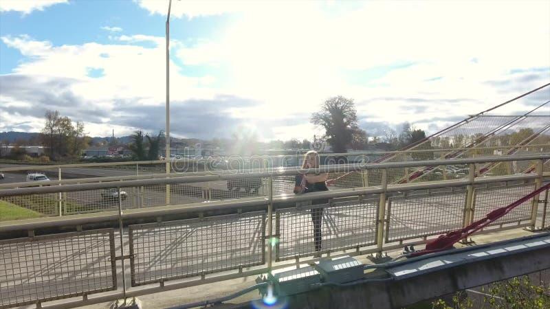 Frau, die auf einer Brücke über einer Autobahn von oben läuft stock video