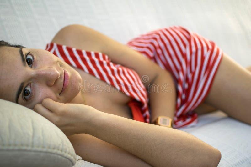 Frau, die auf einer Couch stillsteht ihren Kopf auf einem Kissen und betrachtet Kamera liegt lizenzfreie stockfotos