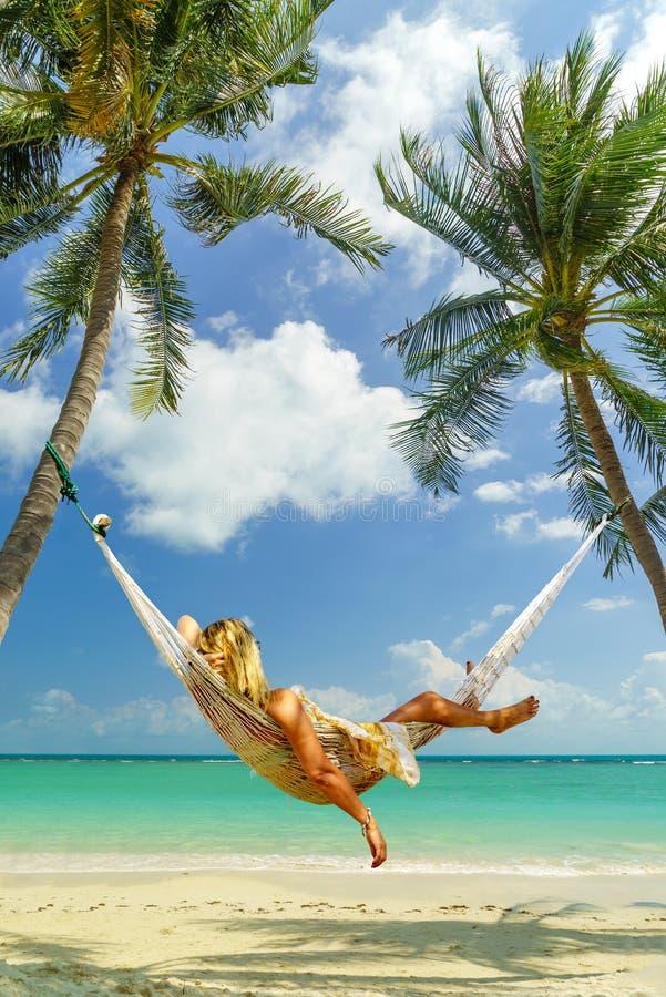 Frau, die auf einer Hängematte am tropischen Strandurlaubsort sich entspannt lizenzfreie stockfotografie
