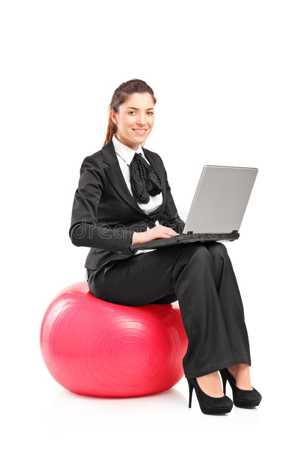Frau, die auf einer Kugel sitzt und an einem Laptop arbeitet stockbilder