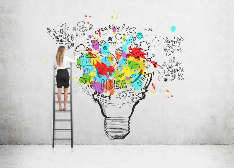 Frau, die auf einer Leiter steht und eine große und bunte Glühlampeskizze auf einer Betonmauer zeichnet stockbilder