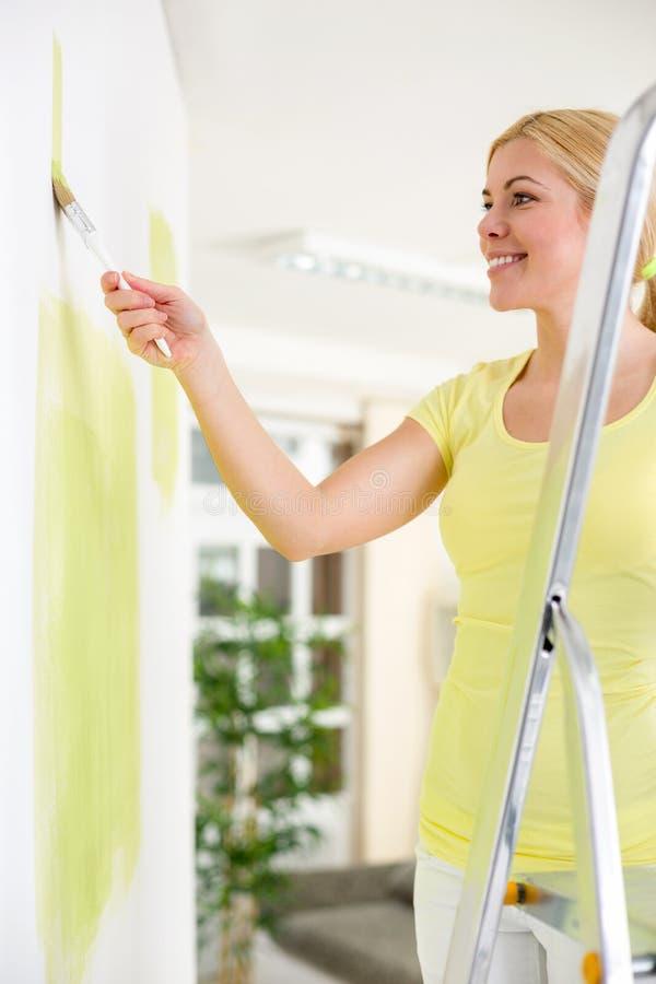 Frau, die auf einer Leiter und einem Malen steht stockbild