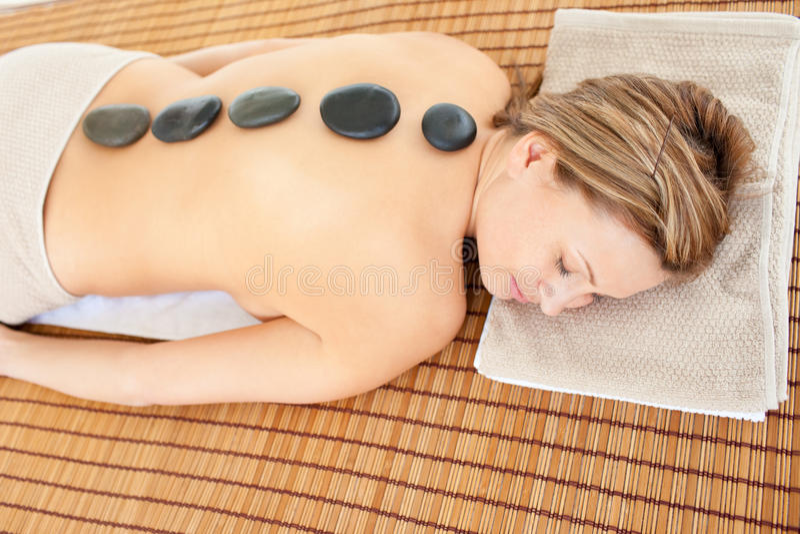 Frau, die auf einer Massagetabelle mit heißen Steinen liegt stockbild