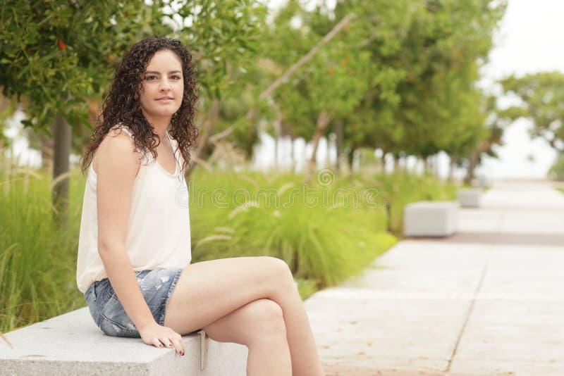 Frau, die auf einer Parkbank sitzt stockfoto