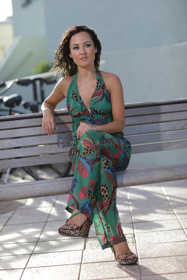 Frau, die auf einer Parkbank sitzt stockbild