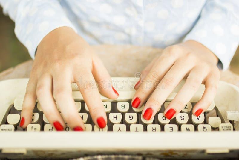Frau, die auf einer Schreibmaschine schreibt stockbilder