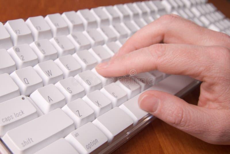 Frau, die auf einer weißen Computer-Tastatur schreibt stockbild