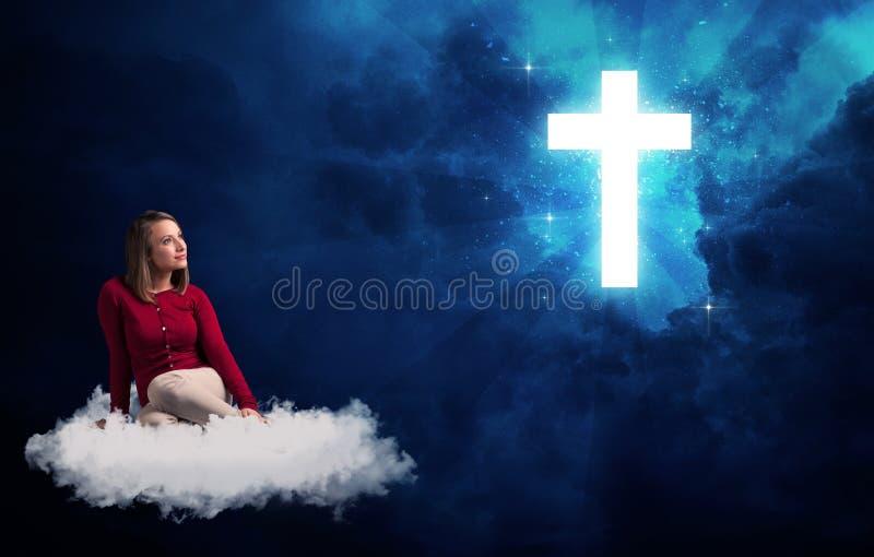 Frau, die auf einer Wolke betrachtet ein Kreuz sitzt lizenzfreie stockfotos