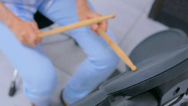 Frau, die auf elektronischem Trommelsatz spielt stockbilder