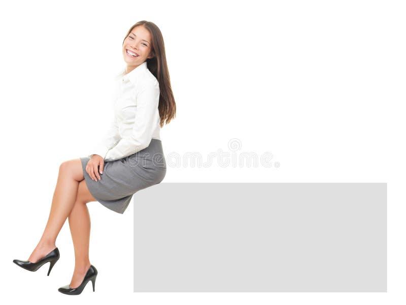 Frau, die auf Fahne sitzt lizenzfreie stockbilder