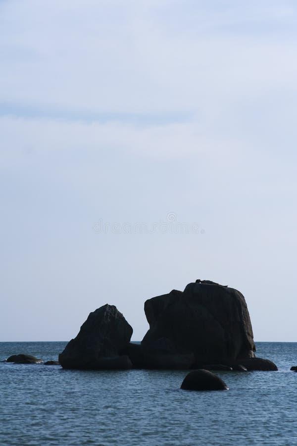 Frau, die auf Felsen ein Sonnenbad nimmt stockbild
