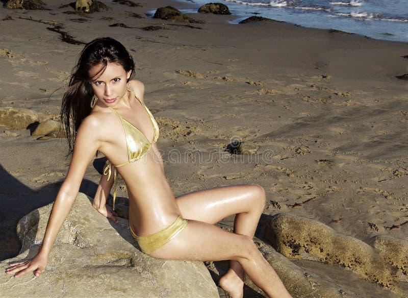 Frau, die auf Felsen an einem Strand liegt lizenzfreie stockbilder