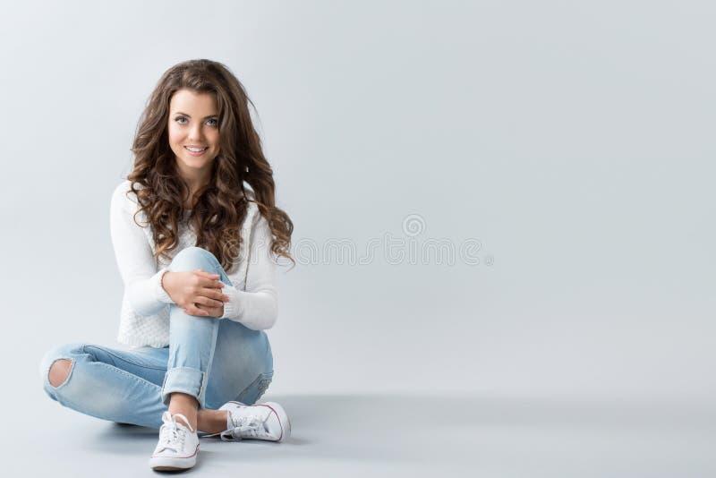 Frau, die auf Fußboden sitzt stockfotos
