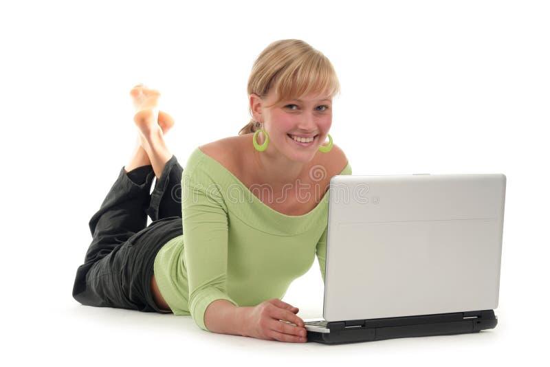 Frau, die auf Fußboden unter Verwendung des Laptops liegt stockbilder