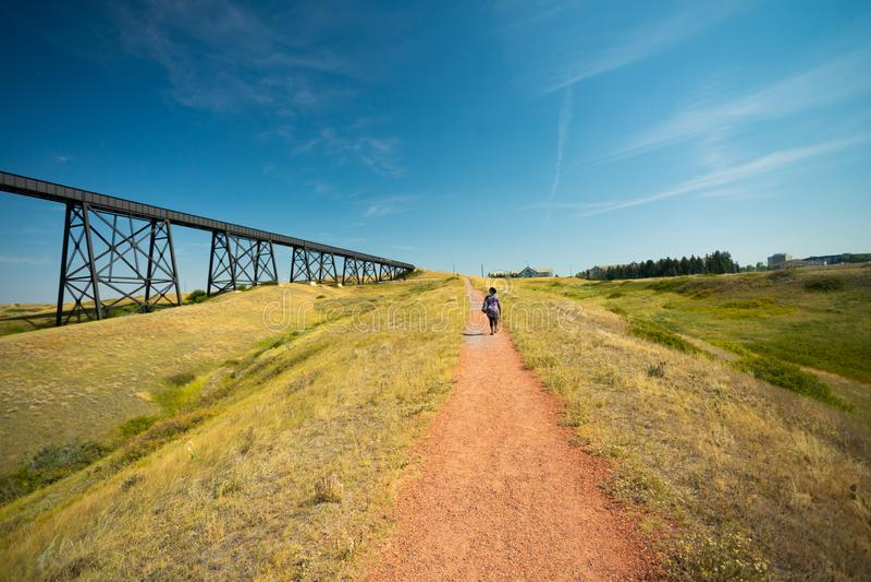 Frau, die auf Fußweg neben Eisenbahnbrücke geht lizenzfreie stockfotos