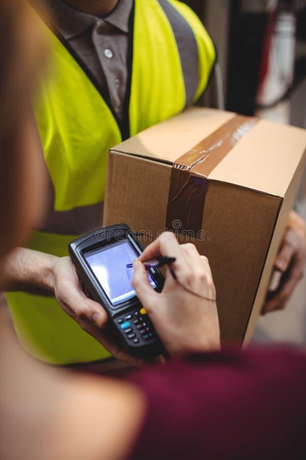 Frau, die auf Gerät zum Lieferungspaket unterzeichnet stockfotografie